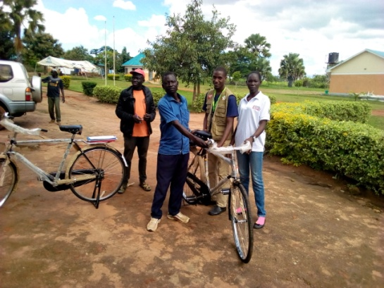 The chairperson of CPC of Lokujo receiving their bicycle.