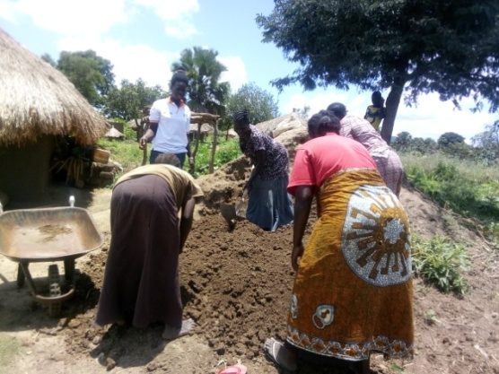 Women mix materials for construction of energy saving stoves