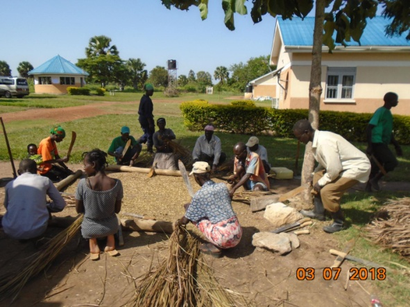 ToTs mixing materials at the base camp prior to construction of the energy saving stoves at Lobule health centre III.