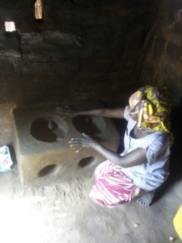 A woman cures her newly constructed Lorena cook stoves in Adranga