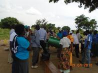 Koboko district representative and a Refugee activiely mixing materials during training on briquette making-Waju 1